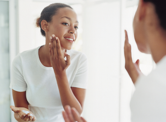 Woman moisturizing her face with NEUTROGENA® products